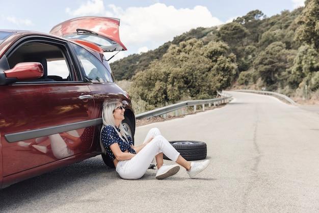 Feliz mujer sentada cerca del coche averiado en la carretera sinuosa
