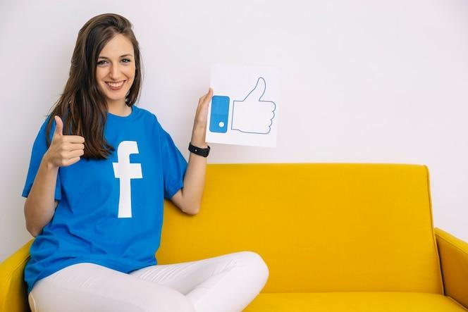 Feliz mujer sentada en el sofá sosteniendo como icono mostrando el pulgar en señal
