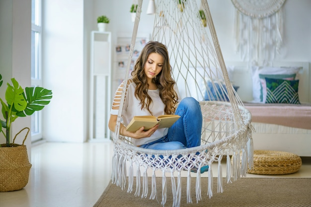 Feliz mujer sentada en una hamaca tejida en la habitación
