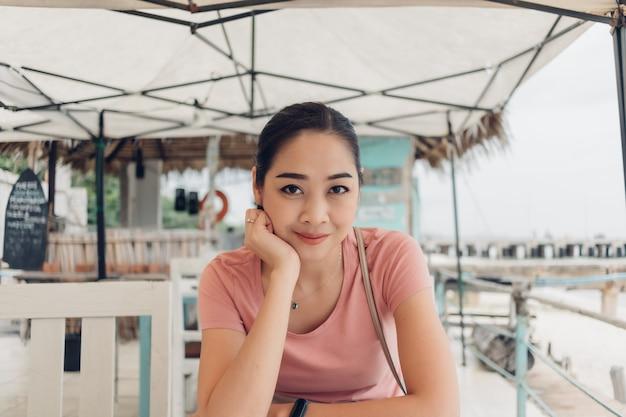 Feliz mujer está sentada en el restaurante en la playa.