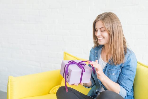 Feliz mujer sentada en el sofá abriendo regalo de san valentín
