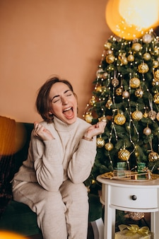 Feliz mujer sentada en el sofá junto al árbol de navidad