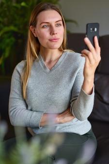 Feliz mujer sentada en el sofá con el portátil y hablando por teléfono en casa.