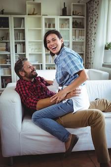 Feliz mujer sentada en la vuelta del hombre en la sala de estar