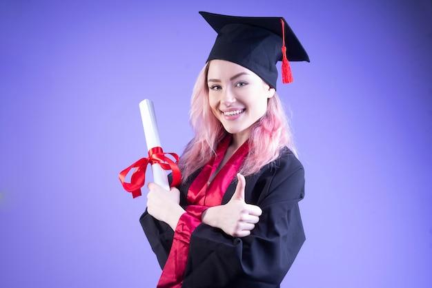 Feliz mujer soltera con gorra de graduación cruzó sus brazos
