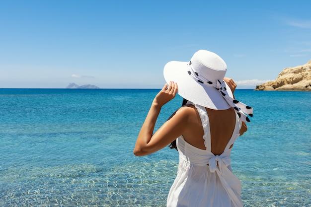 Feliz mujer con un sombrero en una playa tropical