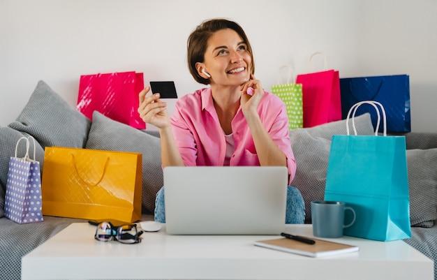 Feliz mujer sonriente en camisa rosa en el sofá en casa entre coloridas bolsas de la compra con tarjeta de crédito pagando en línea en la computadora portátil