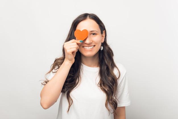 Feliz mujer sonriente está cubriendo un ojo con forma de corazón de papel.