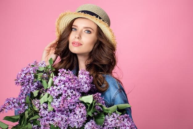 Feliz mujer sonriente disfrutando olor a ramo de flores lilas sobre
