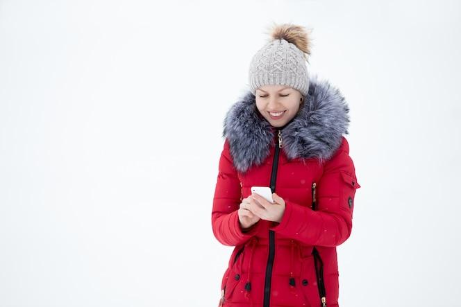 Feliz mujer sonriente en chaqueta de invierno rojo con teléfono móvil, al aire libre contra la nieve
