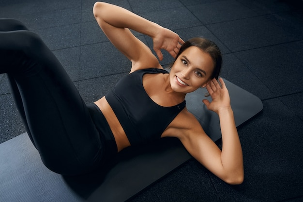 Feliz mujer sonriente entrenando abdominales en el gimnasio
