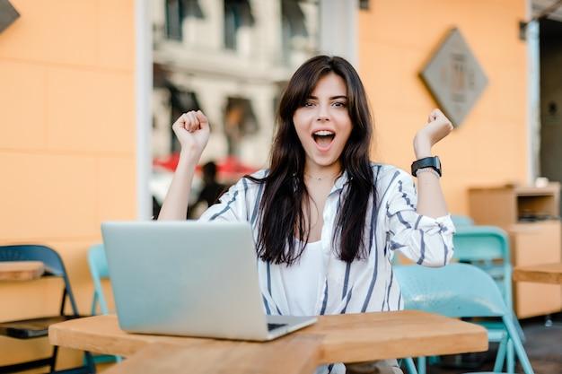 Feliz mujer sonriente con laptop sentada al aire libre en la cafetería