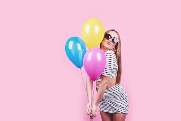 Feliz mujer sonriente está mirando en un aire globos coloridos divirtiéndose sobre un rosa
