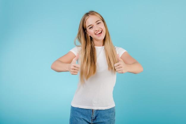Feliz mujer sonriente mostrando pulgares arriba aislado sobre azul