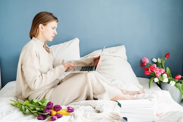 Feliz mujer sonriente sentada en la cama en pijama, con placer disfrutando de las flores, charlando con el portátil