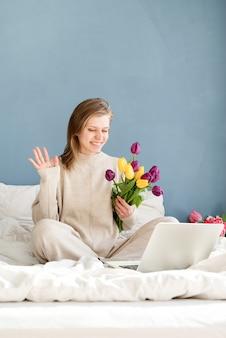 Feliz mujer sonriente sentada en la cama en pijama, con placer disfrutando de las flores, trabajando en la computadora portátil