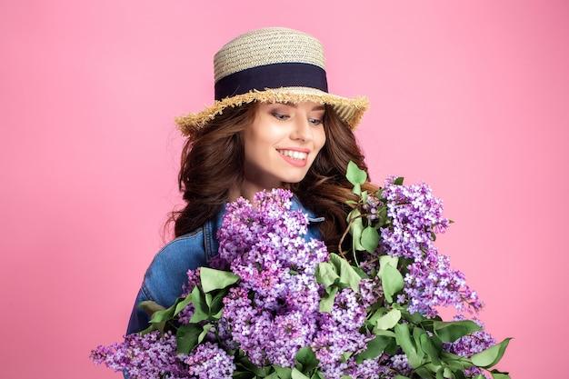 Feliz mujer sonriente en sombrero de paja posando con ramo de flores lilas