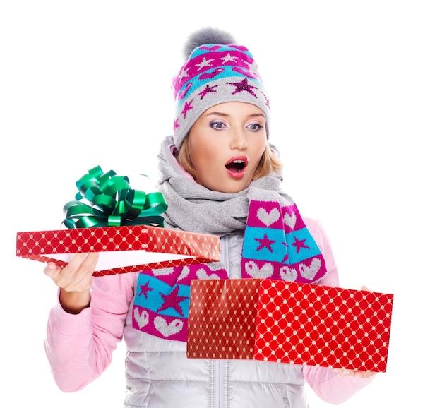 Feliz mujer sorprendida con un regalo de navidad en una ropa de abrigo de invierno aislado en blanco