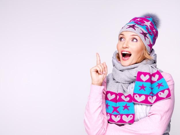 Feliz mujer sorprendida en ropa de invierno con brillantes emociones positivas mirando hacia arriba