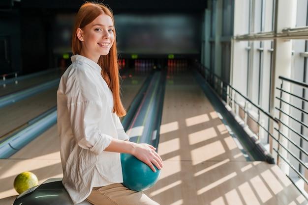 Feliz mujer sosteniendo la bola de boliche