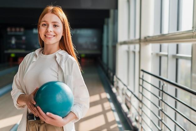 Feliz mujer sosteniendo una bola de bolos turquesa