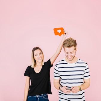 Feliz mujer sosteniendo el icono de amor sobre hombre con teléfono móvil