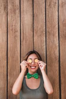 Feliz mujer sosteniendo monedas de oro cerca de los ojos