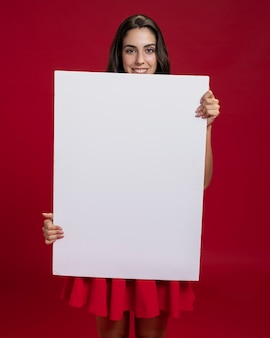 Feliz mujer sosteniendo una pancarta vacía