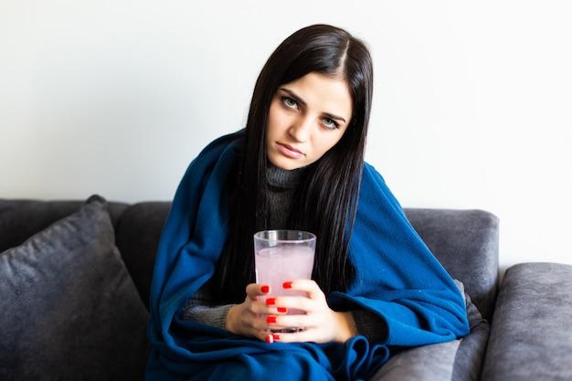 Feliz mujer sosteniendo una pastilla redonda blanca y un vaso de agua mirando a la cámara sentada en un sofá