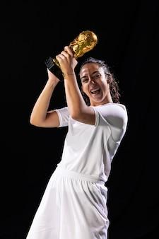 Feliz mujer sosteniendo el trofeo de fútbol