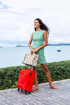 Feliz mujer turista elegante pelo bastante largo caucásico vestido con maleta roja fuera del hotel