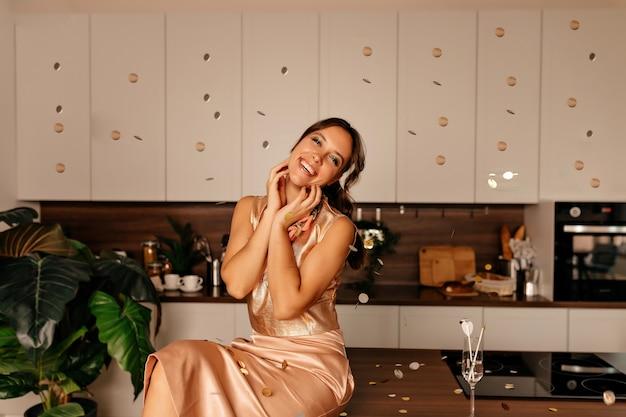 Feliz mujer vestida con camiseta brillante y falda rosa posando en la cocina con confeti