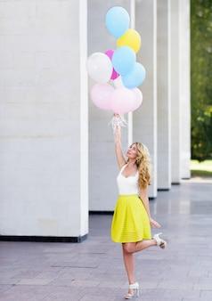 Feliz mujer en vestido amarillo con globos de colores