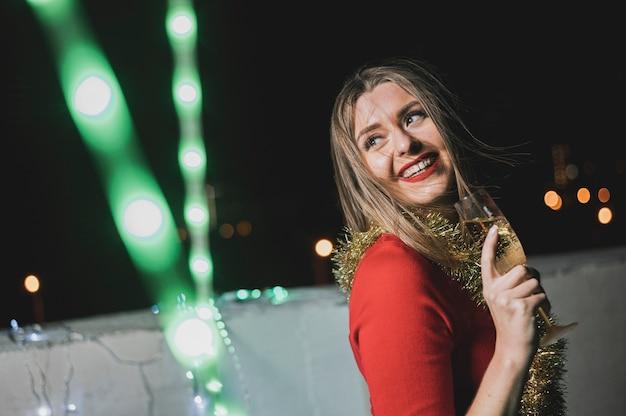 Feliz mujer en vestido rojo con lámparas brillantes
