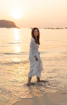 Feliz mujer va de viaje en la playa tropical de arena en verano