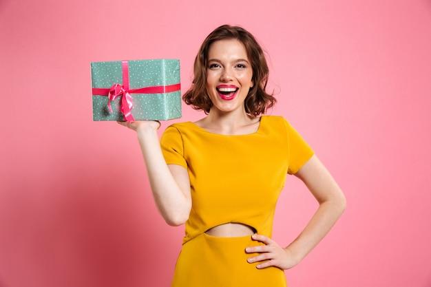 Feliz mujer ypung con la mano en la cintura con caja de regalo,