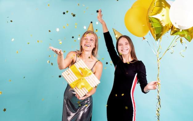 Feliz, mujeres jóvenes, en, cumpleaños, sombreros, celebrar cumpleaños