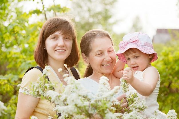 Feliz las mujeres y el niño en el jardín de verano