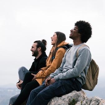 Feliz multi étnica joven pareja sentada en roca disfrutando juntos