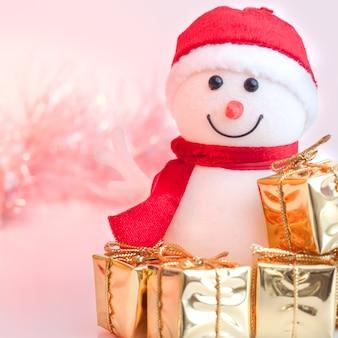Feliz navidad, año nuevo, muñeco de nieve, regalos en cajas doradas sobre un fondo de bokeh rosa y amarillo.