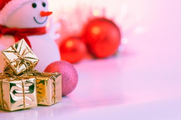 Feliz navidad, año nuevo, muñeco de nieve, regalos en cajas de oro y bolas rojas sobre un fondo rosa.