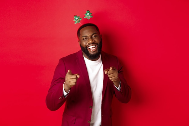 Feliz navidad. apuesto hombre afroamericano en blazer y diadema de fiesta, celebrando el año nuevo, apuntando a la cámara y sonriendo, felicitando, fondo rojo