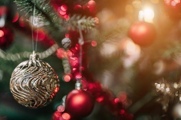 Feliz navidad, cerca de bolas de colores, caja de regalos y decoración de paquete de imagen de felicitación de navidad sobre fondo de árbol de navidad verde decoración durante navidad y año nuevo.