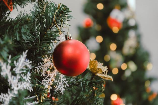 Feliz navidad. cerrar bola decorada de color rojo colgando en navidad con fondo claro bokeh