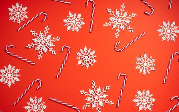 Feliz navidad dulces y copos de nieve blancos sobre fondo rojo.