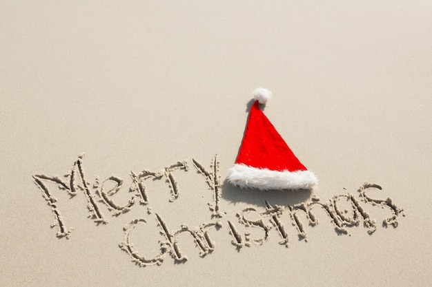 Feliz navidad escrita en la arena con el sombrero de santa