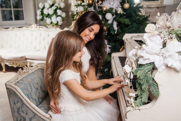 Feliz navidad y felices fiestas. alegre madre y su hija linda niña en interior clásico blanco jugando en un piano blanco decorado árbol de navidad. año nuevo