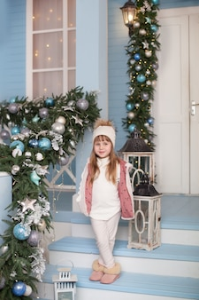 Feliz navidad, felices fiestas! año nuevo 2020. niña se encuentra en el porche de la casa decorada para navidad. niño decora terraza para año nuevo. navidad decorado terraza al aire libre con guirnaldas.