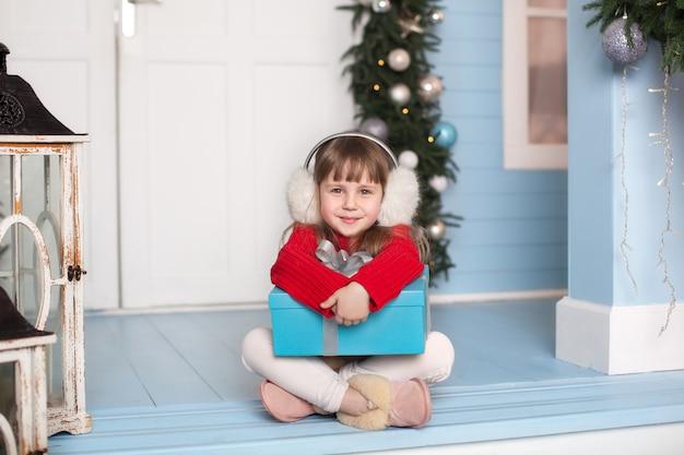 Feliz navidad, felices fiestas! año nuevo. niña sentada en suéter rojo con regalo en el porche de la casa. el niño se sienta en la terraza decorada para navidad y juega en el patio de invierno. el niño abre el presente.
