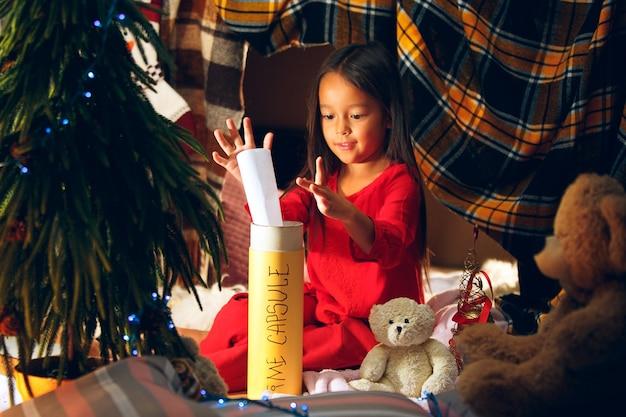 Feliz navidad y felices fiestas. niña linda escribe la carta a santa claus cerca del árbol de navidad